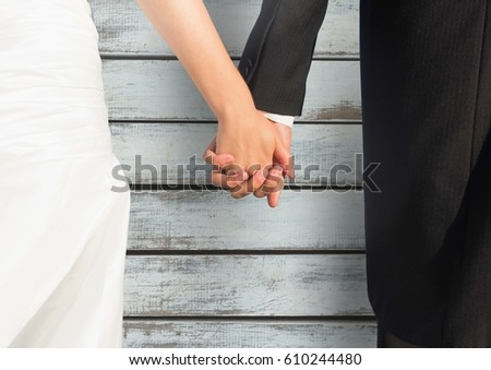 Digital composite of Wedding couple holding hands against wood