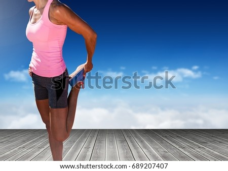 Digital composite of Woman stretching leg in front of sky