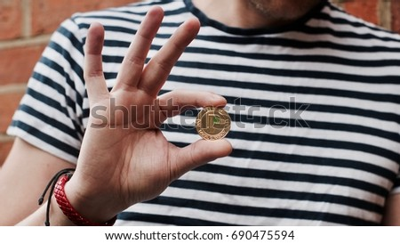 Digital currency physical gold peercoin coin in man hand near brick wall.