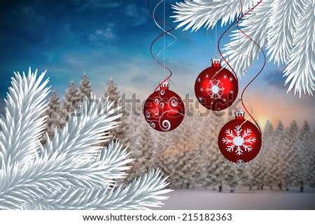 Digital hanging christmas bauble decoration against fir tree forest in snowy landscape