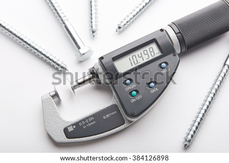 Digital micrometer with adjustable pressure measurement with steel screws isolated on white background. Measurement of details in the bolts and nuts industry. - stock photo