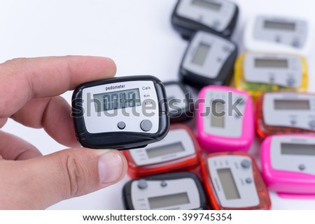Digital pedometer in the hand over pile of pedometers. - stock photo