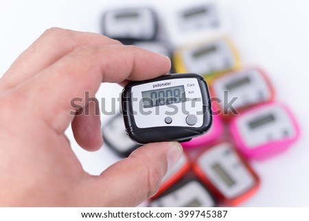Digital pedometer in the hand over pile of pedometers.