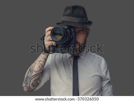 Digital photographer in white shirt and casual hat. Isolated on grey background. - stock photo