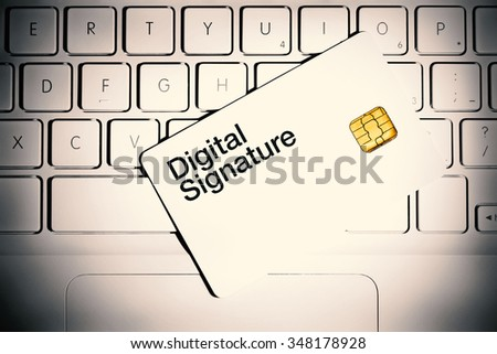 Digital Signature concept. Smart card on a keyboard of white laptop computer. - stock photo