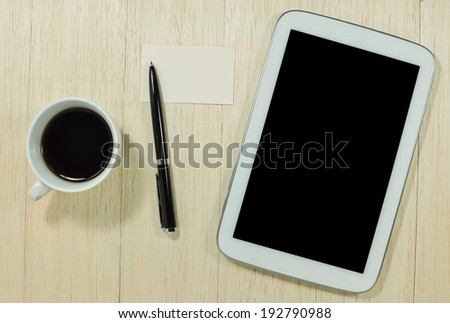 Digital tablet  and cup of coffee with business card on wooden table.