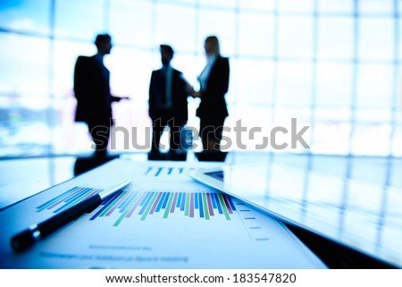 Digital tablet and financial document with pen at workplace on background of three business partners interacting - stock photo