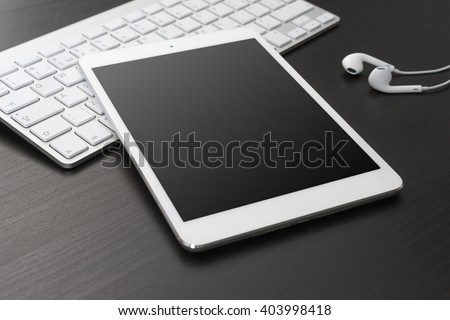 Digital tablet and headphones on a dark table.