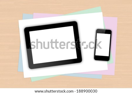 Digital tablet and smart phone with blank white screen on colorful note papers on wooden table. - stock photo