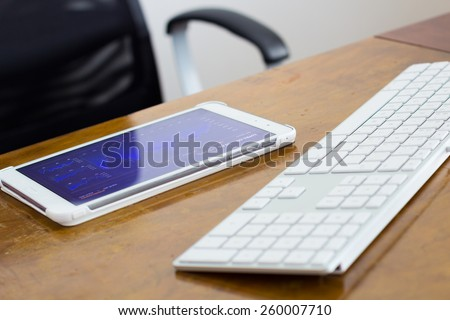 Digital tablet and white keyboard on wooden desk before a chair - stock photo