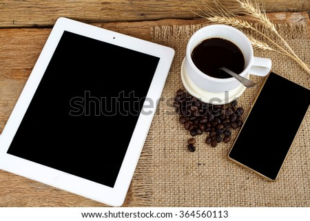 digital tablet cellphone and cup of coffee on old wooden desk. Simple workspace or coffee break in morning/ selective focus