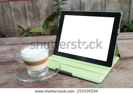 Digital tablet computer and cup of coffee on old wooden desk. Simple workspace or coffee break with web surfing. - stock photo