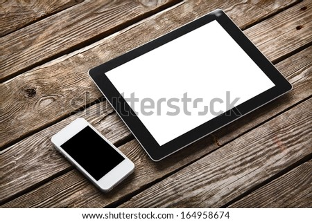 Digital tablet computer and white smart phone with isolated screens on old wooden desk. - stock photo