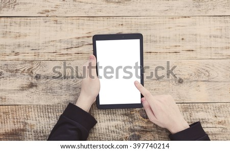 Digital tablet computer, isolation screen in male hands over cafe background - table wooden planks, cup of coffee, notebook, pencil, vintage camera. Hipster style. Top view with copy space. - stock photo