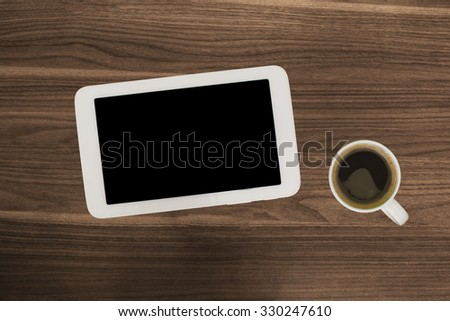 Digital tablet computer or smartphone phone with cup of fresh coffee on wooden desk. Simple workspace or coffee break with web surfing. A lot of free spare copyspace for content