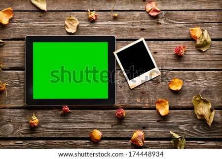 Digital tablet computer with blank instant photo and rose petals on old wooden desk. - stock photo