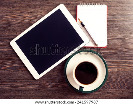 Digital tablet computer with cup of coffee on old wooden desk. Simple workspace or coffee break with web surfing