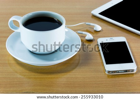 Digital tablet computer with  cup of coffee on old wooden desk. Simple workspace or coffee break with web surfing. - stock photo