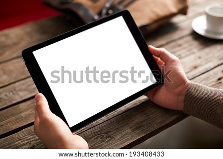 Digital tablet computer with isolated screen in male hands over cafe background
