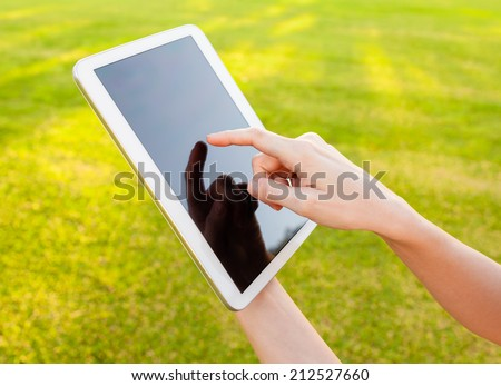 Digital tablet computer with isolated screen in woman hands - stock photo