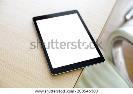 Digital tablet computer with isolated screen on office desk. At office interior.