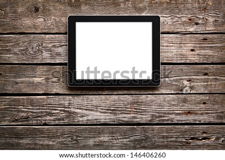 Digital tablet computer with isolated screen on old wooden desk. - stock photo