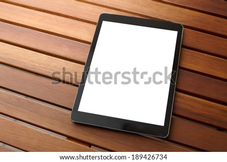 Digital tablet computer with isolated screen on wooden desk. - stock photo