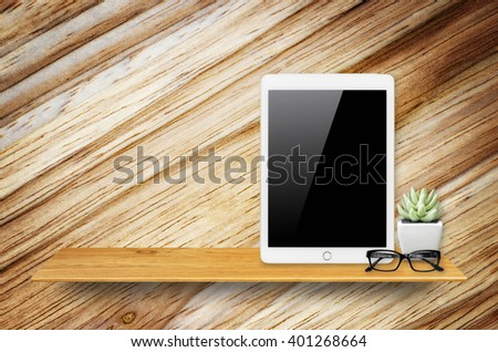Digital tablet computer with isolated screen with clipping path on bookshelf in the wall.
