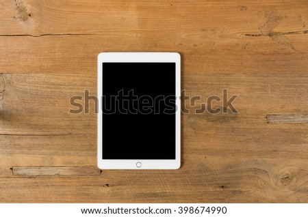 Digital tablet computer with isolated screen with clipping path on wooden background. - stock photo
