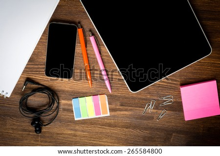 Digital tablet computer with note paper and cup of coffee on old wooden desk. Simple workspace or coffee break with web surfing. - stock photo