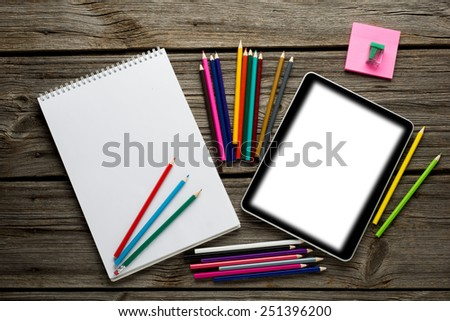 Digital tablet computer with paper note book and colorful pencils on old wooden desk. Simple workspace with web surfing.  - stock photo