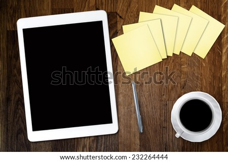 Digital tablet computer with sticky note paper and cup of coffee on old wooden desk. Simple workspace or coffee break with use of web .