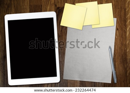 Digital tablet computer with sticky note paper and cup of coffee on old wooden desk. Simple workspace or coffee break with use of web . - stock photo