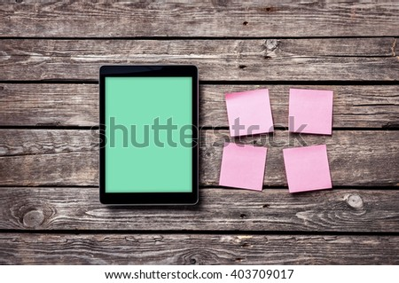 Digital tablet computer with sticky notes on wooden desk. Clipping path for display included.