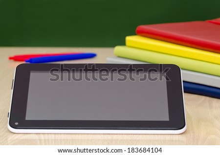 digital tablet leaning against a colorful notebooks,on a school desk  - stock photo