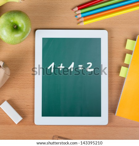 Digital tablet on a school desk with math exercise between a paper notebook, pencils, an eraser, and an apple - stock photo