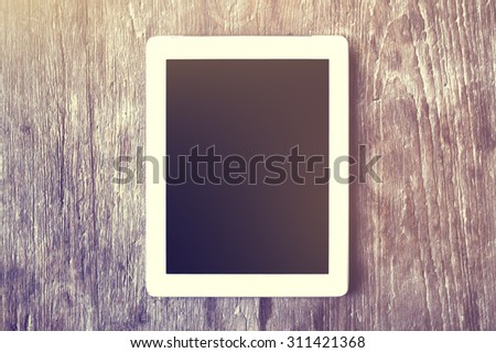 Digital tablet on a wooden table - stock photo