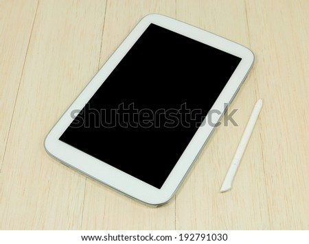 Digital tablet on wooden table.
