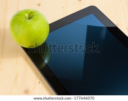 digital tablet pc and green apple on wood table, concept of learn new technology