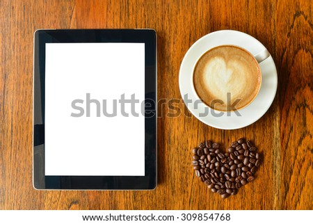 Digital tablet pc ipad and a cup of coffee with heart shape on wood background