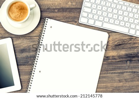 digital tablet pc, keyboard and cup of coffee on wooden table. retro style toned picture - stock photo