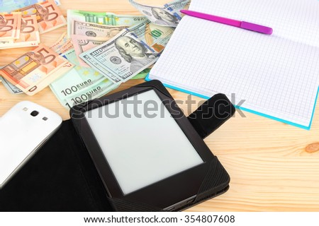Digital tablet, smart phone and classic notebook with pen on the wood desktop with money (banknotes euro and USA dollars) in the background. Modern gadgets and retro office accessories with money  - stock photo