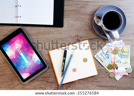 Digital tablet, sticky note paper, cup of coffee and money on old wooden desk. Simple workspace or coffee break with web surfing. - stock photo