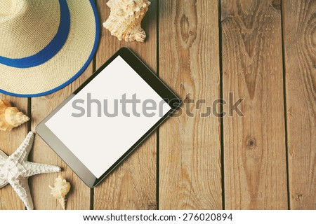 Digital tablet, summer hat and seashells on wooden background - stock photo
