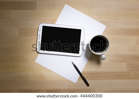Digital Tablet,White A4 Paper and Black Silver Pen, Espresso Mug or Cup on Wood Texture Office Desk or Table with Close Up And Details, View from Top or Above.