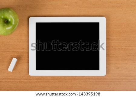 Digital tablet with a black empty display over a school desk next to an eraser and a green apple - stock photo