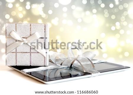 Digital tablet with christmas present on defocused lights - stock photo