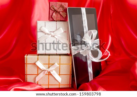 Digital tablet with christmas presents on red background - stock photo
