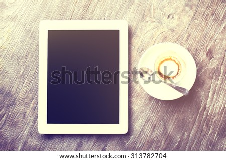Digital tablet with cup of coffee on a wooden table - stock photo