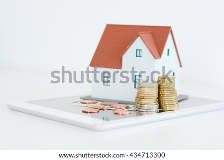 Digital tablet with house model and stack of coins